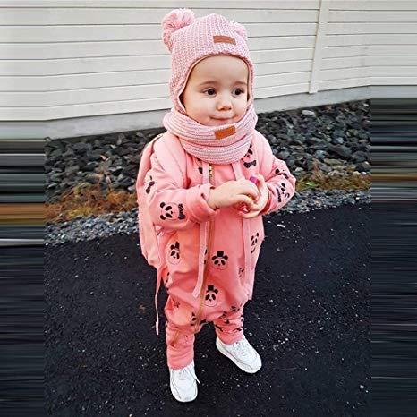 Kleines Mädchen mit rosa Panda-Overall und Mütze