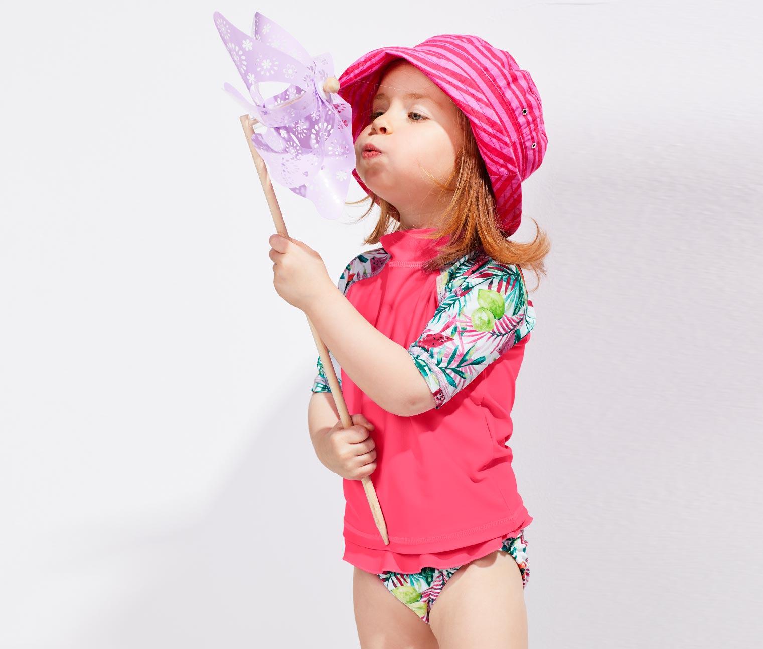Mädchen mit Windrad und UV Schutzkombi