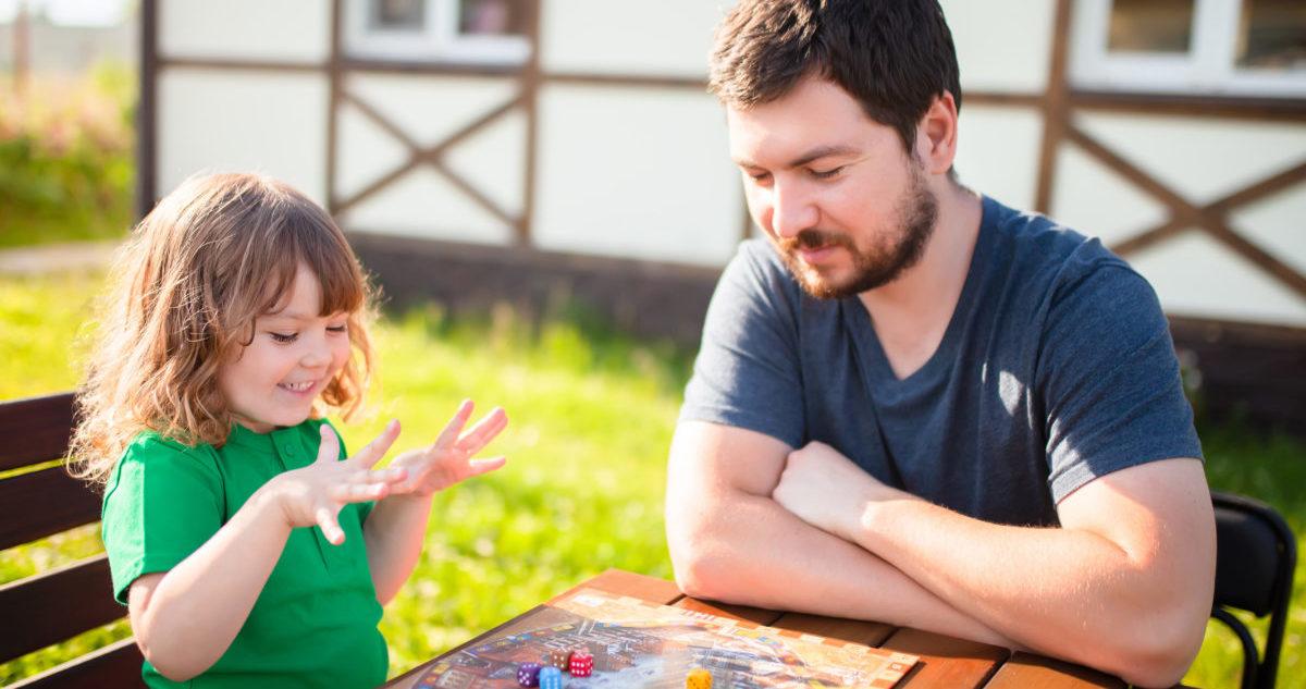 Mädchen spielt mit Vater Brettspiel