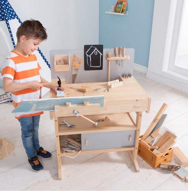 Junge an Spiele-Werkbank aus Holz