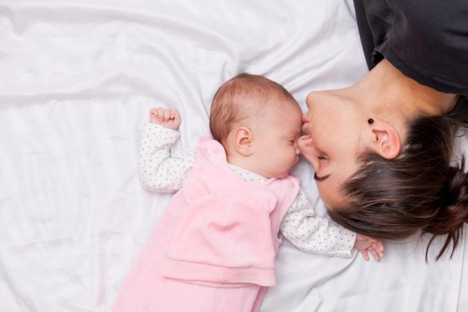 Mama küsst Baby auf die Stirn