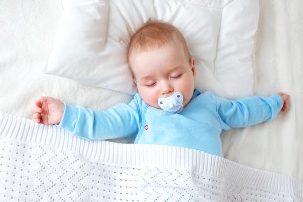 Baby schläft mit Decke und Kissen
