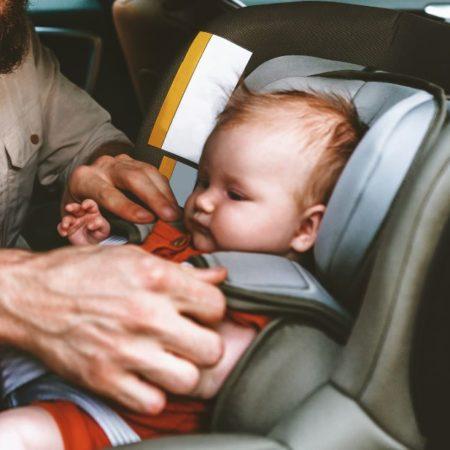 Mann schnallt Baby in Kindersitz an