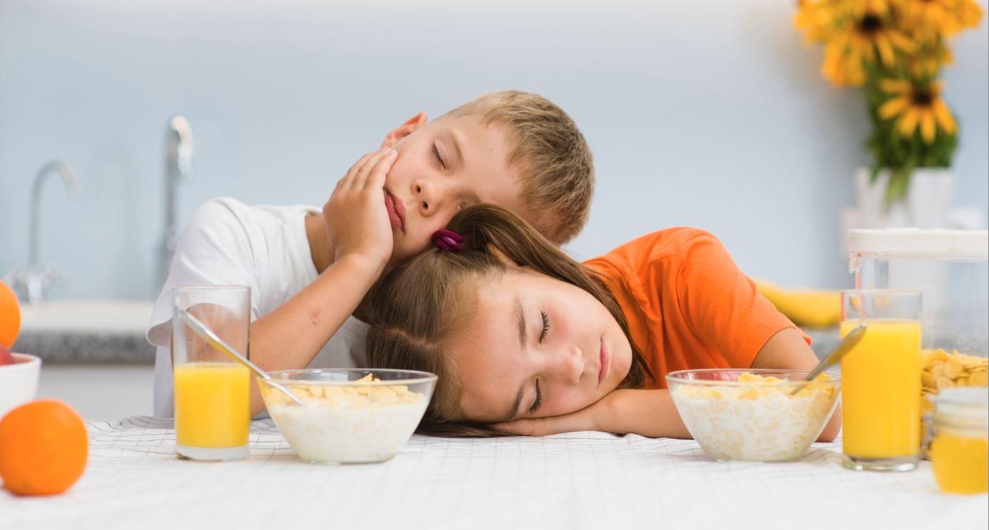 Kinder schlafen am Frühstückstisch