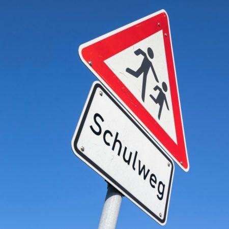 Schulweg Schild vor blauem Himmel