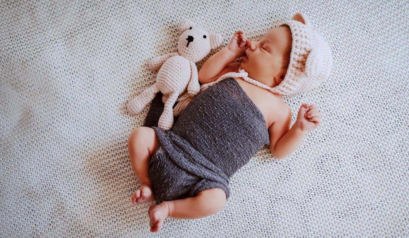 Baby mit Strickteddy und Strickmütze