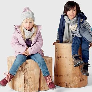 Kleinkinder in Winterklamotten sitzen auf Baumstamm