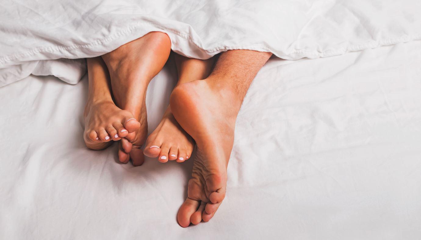 Füße gucken aus dem Bett raus