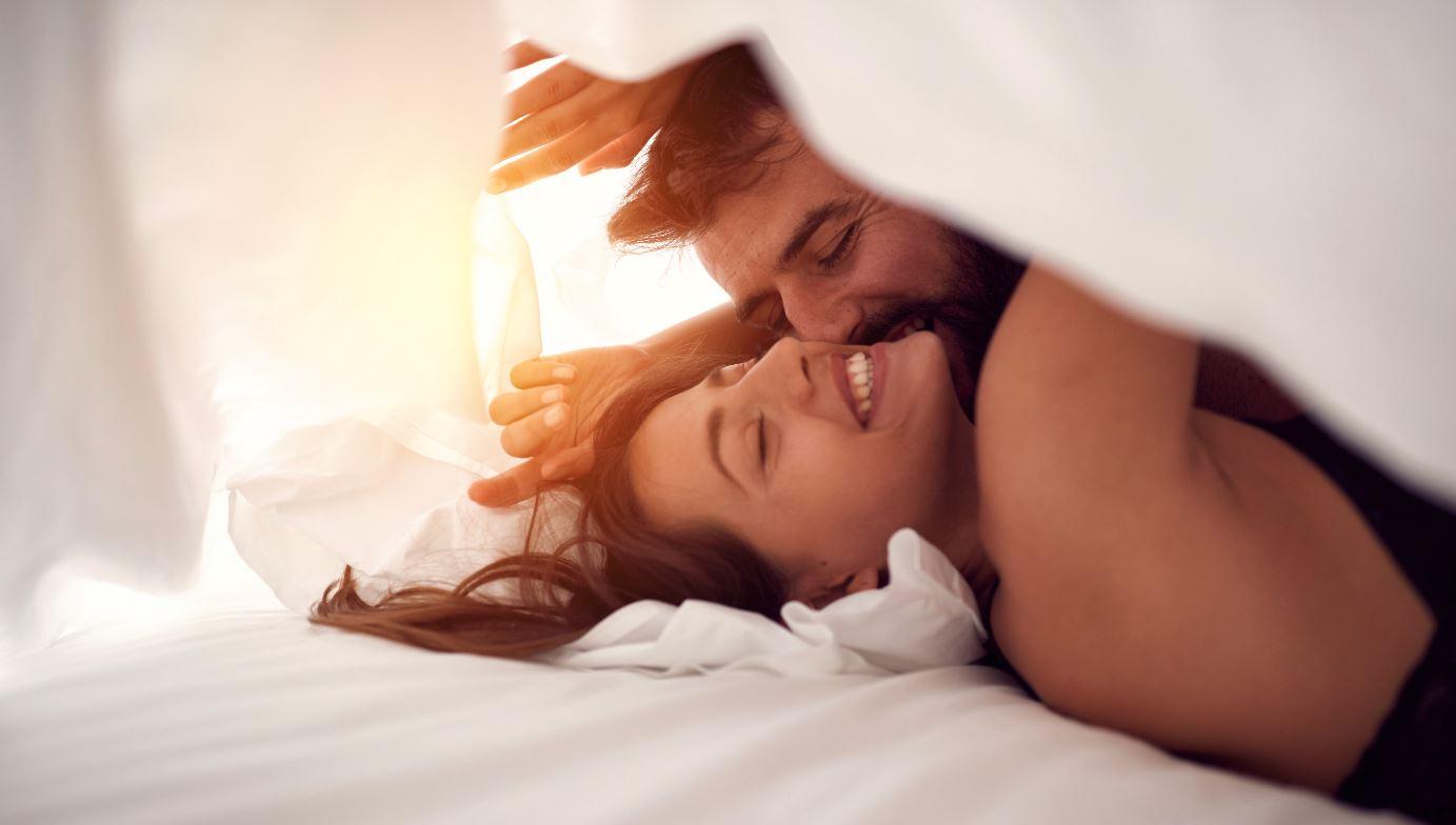 Mann und Frau liegen im Bett und albern rum