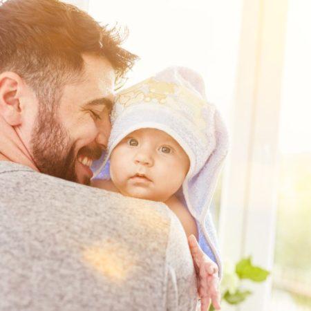 Papa trägt Baby nach Erkältungsbad