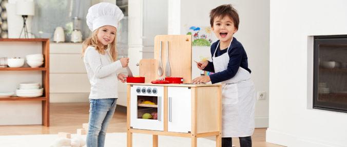 Junge und Mädchen spielen in Spielküche