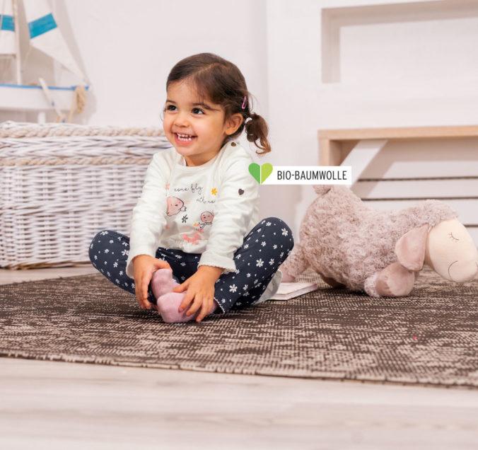 Kleinkind sitzt auf dem Boden und lacht