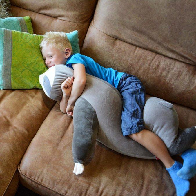 Junge kuschelt mit Faultierkissen