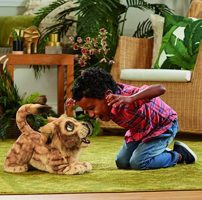 Junge spielt mit Stofflöwe