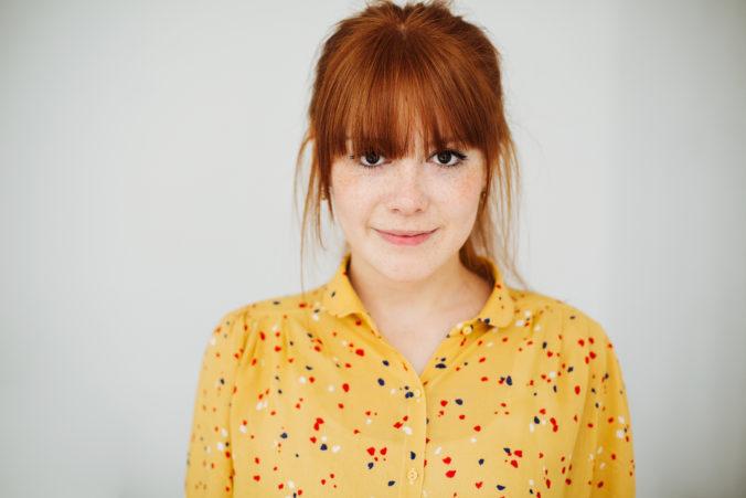 Frau mit roten Haaren und gelber Bluse