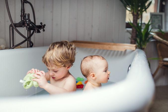 Kleinkind und Baby spielen in der Badewanne