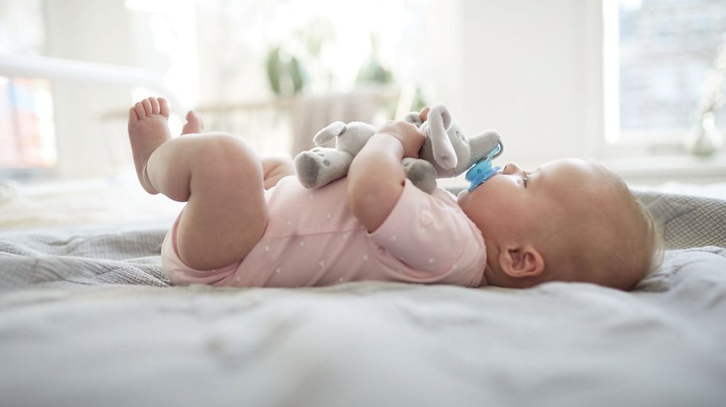 Baby mit Schnullerkuscheltier
