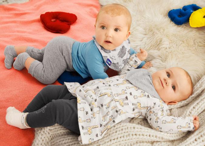 Zwei Babys liegen auf Decke