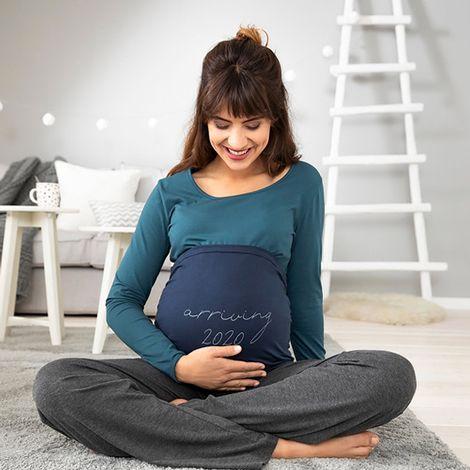 Schwanger Frau mit Bauchband mit Aufdruck Arriving 2020