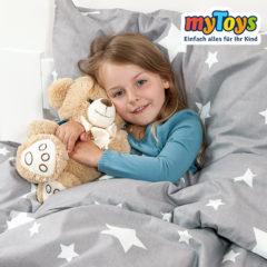 Mädchen liegt in grauer Bettwäsche mit Sternen
