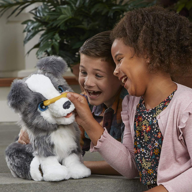 Junge und Mädchen spielen mit Plüschhund von Hasbro