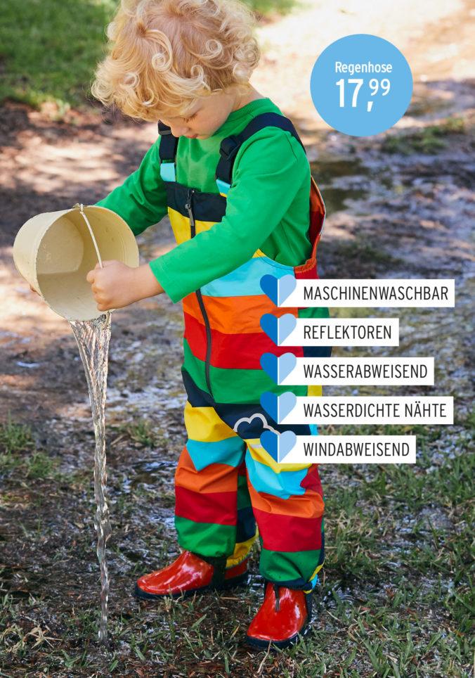 Junge in Regenbekleidung mit Wassereimer