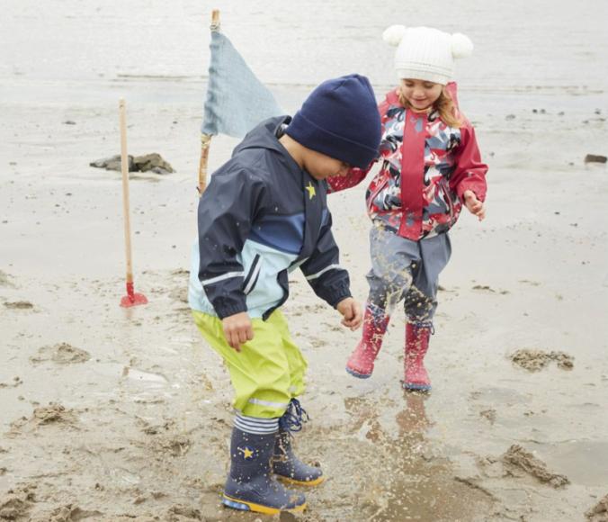 Mädchen und Junge spielen im Matsch