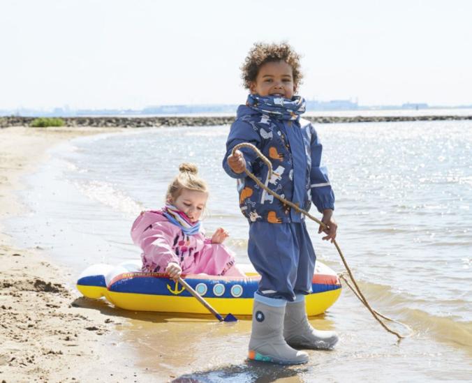 Junge und Mädchen spielen in Matschklamotten am Strand