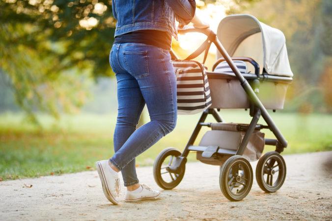 Frau geht in der Natur mit Kinderwagen spazieren
