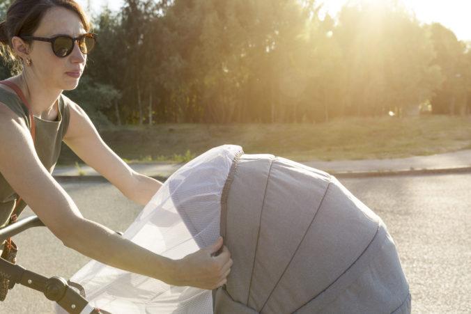 Frau mach Sonnenverdeck über Kinderwagen