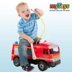 Junge sitzt auf Spielzeugfeuerwehrauto