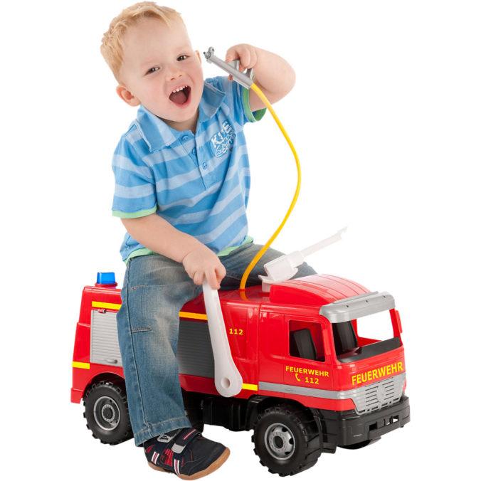 Kind sitzt auf Spielzeugfeuerwehrauto