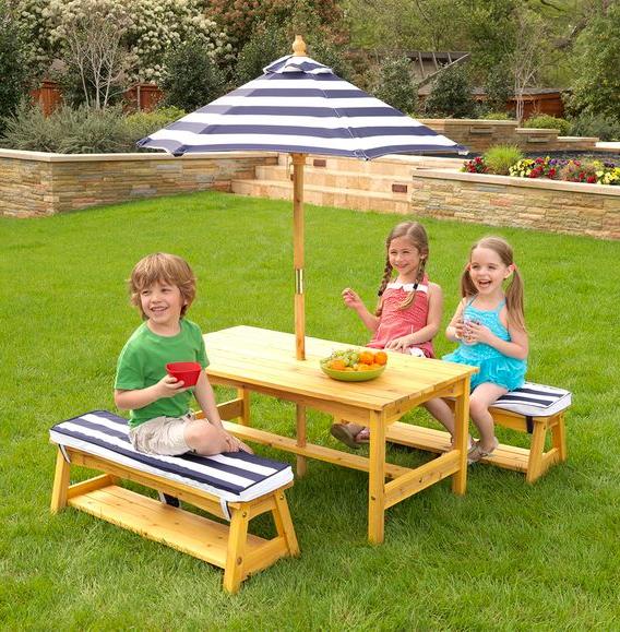 Kinder sitzen an einem Kindertisch im Garten