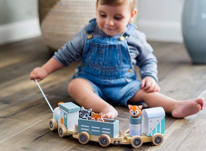 Junge spielt mit Holzeisenbahn