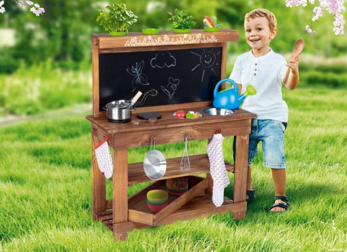 Junge spielt mit Holzkueche im Garten