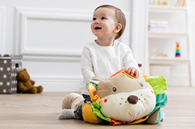 Kleinkind spielt mit großem Kuscheltier