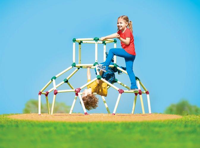 Kinder spuelen an einem Klettergerüst