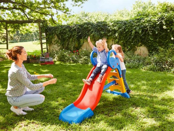 Kinder spielen auf einer Rutsche im Garten