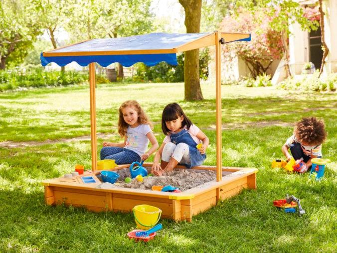 Mädchen spielen in Sandkasten