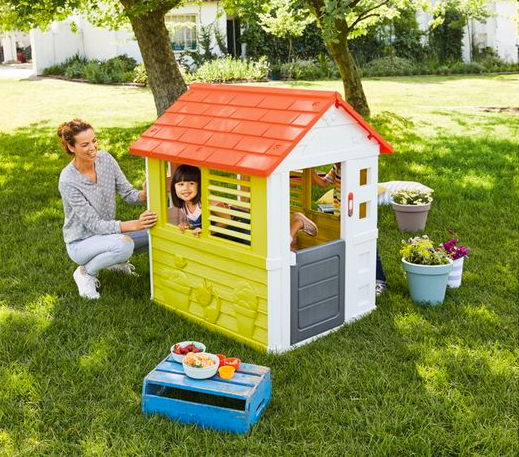 Mutter und Tochter spielen in Spielhaus im Garten