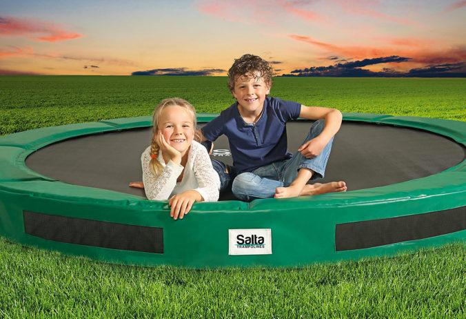 Kinder sitzen auf Trampolin, das in den Boden eingelassen ist