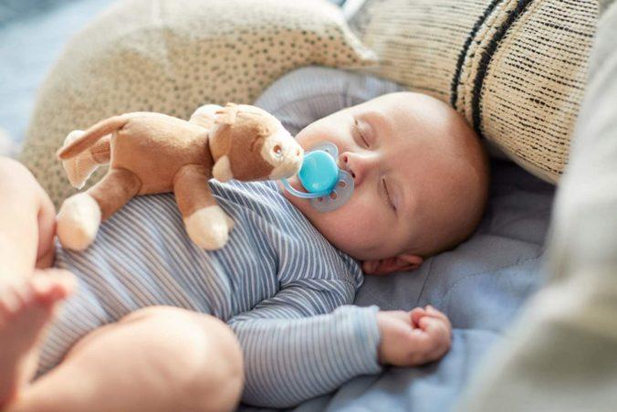 Baby mit Schnuller und Kuscheltier