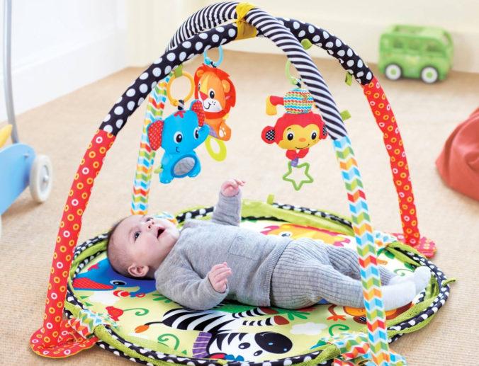Baby liegt unter Activitydecke