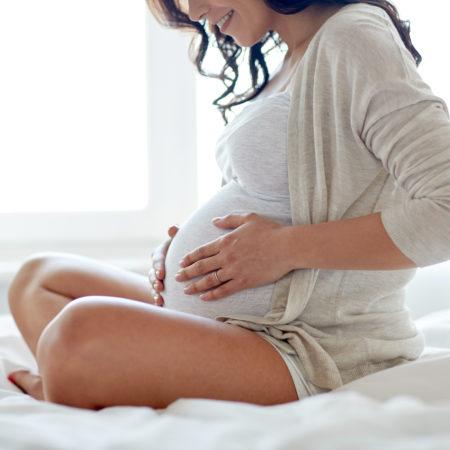 Schwangere sitzt auf dem Bett
