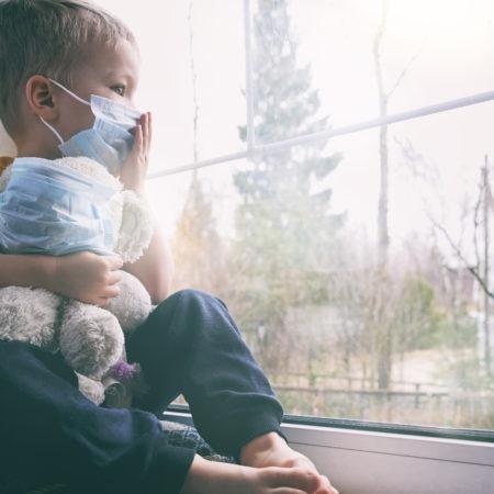 Kidn mit Maske und Teddybär