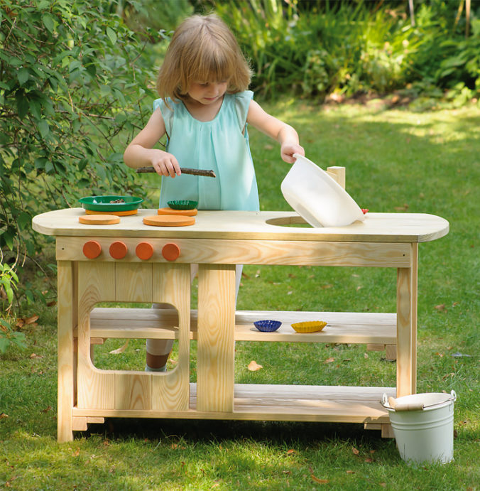 Mädchen spielt in Outdoor-Spielküche