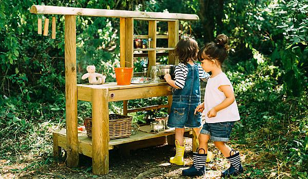 Kinder spielen in Matschküche im Garten