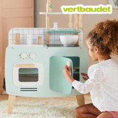 Mädchen spielt mit Spielküche im Retro-Stil