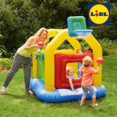Kinder spielen mit Hüpfburg im Garten