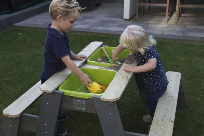 Kinder im Garten am Spieltisch